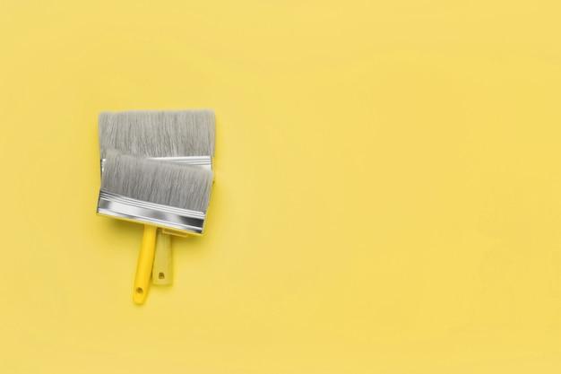 Verfborstels - bovenaanzicht op geel. trendy 2021 jaar ultimate grey en oplichtende kleuren. kopieer ruimte.
