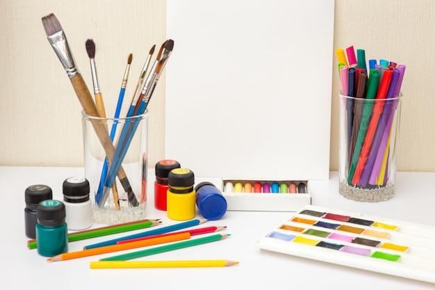 Verfborstels en kleurrijke tekeningslevering op witte lijst. bespotten