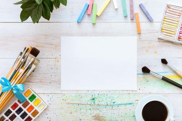 Verfborstels, paintbox met aquarellen, kleurpotloden, koffie en blanco papier op witte houten achtergrond, artistieke achtergrond, creatieve kunstenaarsstudio, bovenaanzicht van boven, plat met kopie ruimte