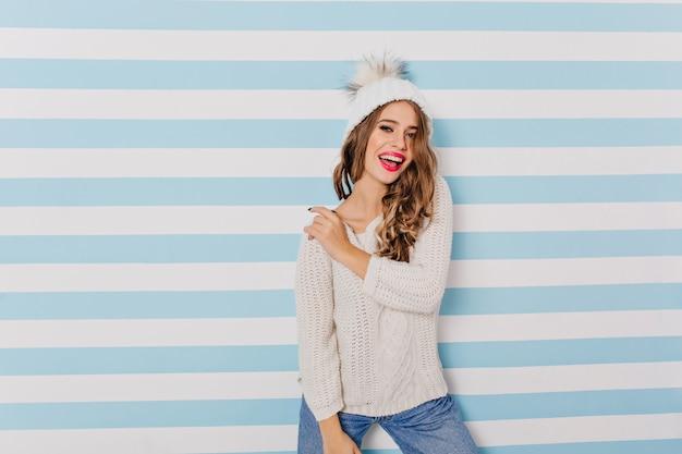 Verfijnd, energiek meisje in trendy winter trui en muts kijkt vrolijk en poseert voor portret binnenshuis