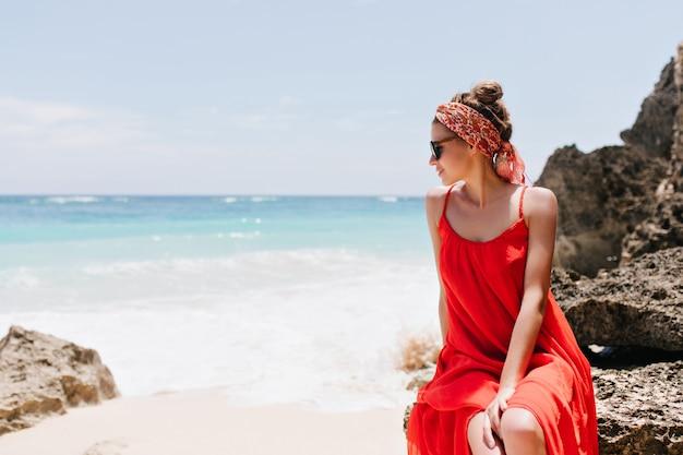 Verfijnd kaukasisch vrouwelijk model zittend op steen en genietend van uitzicht op zee. romantische witte jonge vrouw die door zonnebril oceaan bekijkt.