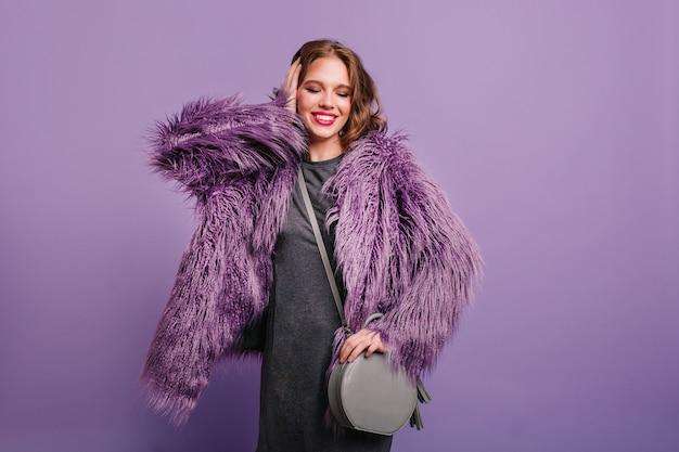 Verfijnd krullend meisje met trendy make-up staande met gesloten ogen op paarse achtergrond