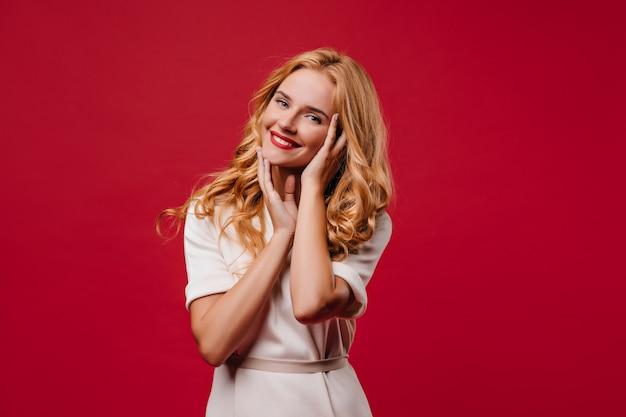 Verfijnd langharig meisje dat haar gezicht met een glimlach aanraakt. aantrekkelijke blonde vrouw die zich op rode muur bevindt