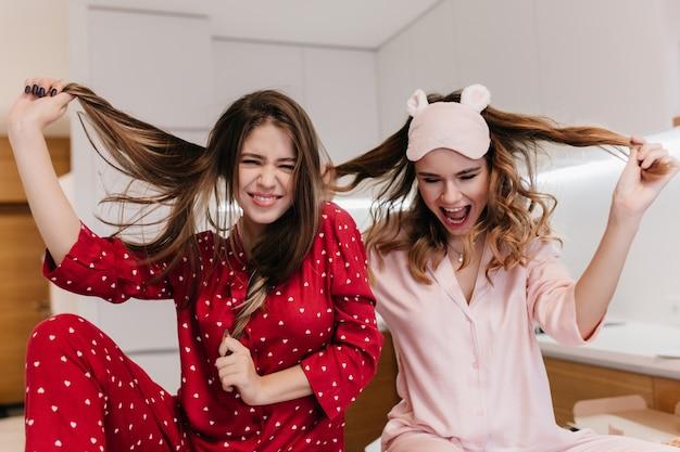 Verfijnd meisje in roze slaapmasker dat met haar krullend haar speelt. binnenportret van innemende zusters die vroeg in de ochtend voor de gek houden.