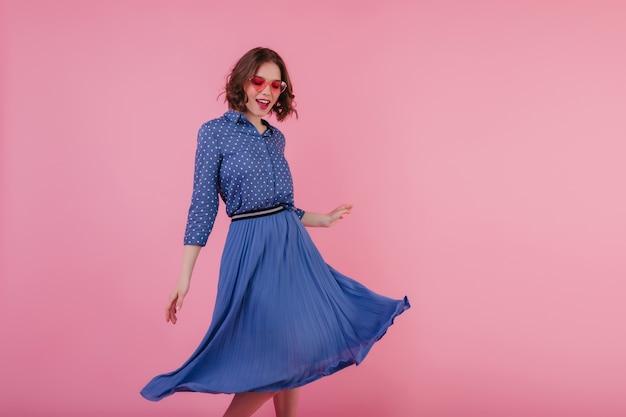 Verfijnd wit meisje met golvend haar dat op roze muur danst. innemende europese dame draagt blauwe midi-rok en blouse.