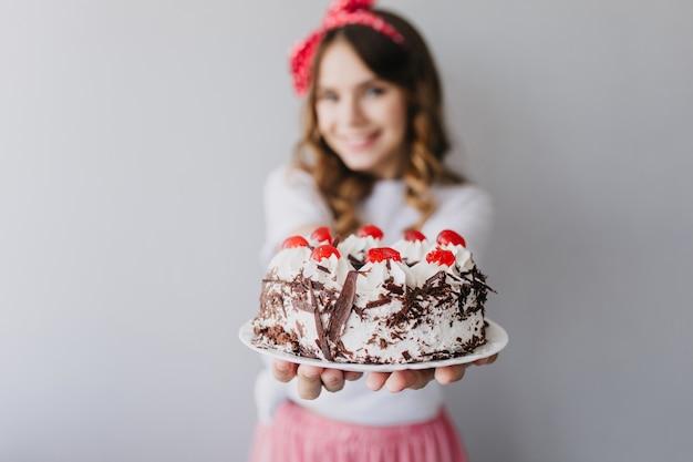 Verfijnde blanke vrouw die smakelijke cake met bessen toont. binnenportret van overweldigend feestvarken met romige pastei.