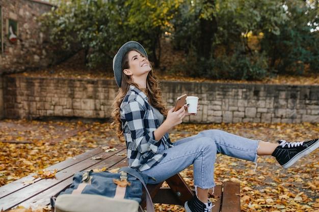 Verfijnde blanke vrouw in stijlvolle vrijetijdskleding tijd doorbrengen op platteland in herfstdag