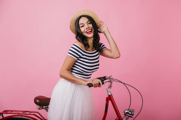 Verfijnde latijns-vrouw in gestreept t-shirt emotioneel poseren. schitterend donkerbruin meisje in hoed die zich met fiets bevindt.
