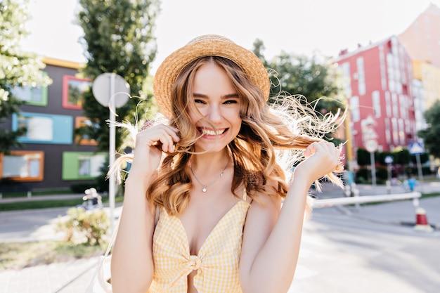 Verfijnde, licht gebruinde dame die op straat positieve emoties uitdrukt. fascinerend meisje in hoed dansen in de ochtend.