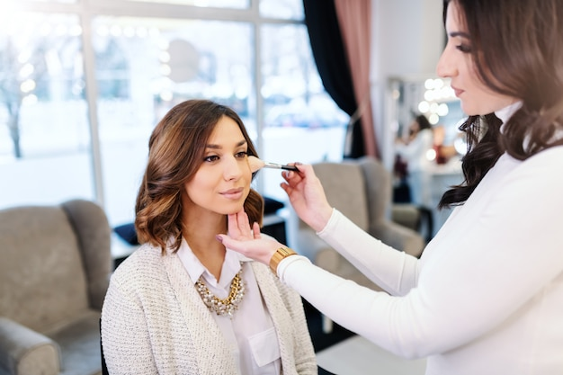 Verfijnde mooie kaukasische brunette zitten in de schoonheidssalon terwijl make-up artiest blozen zetten op de wangen van de vrouw.
