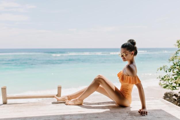 Verfijnde slanke jonge vrouw poseren op het strand. aangenaam gelooid meisje in zonnebril en stijlvol zwempak chillen aan de kust van de oceaan met een verlegen glimlach.