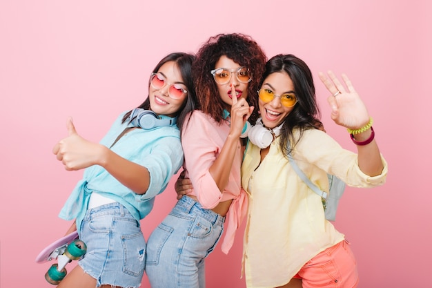 Verfijnde spaanse vrouw in kleurrijke armbanden die hand met vrienden golven. mooie aziatische dame in stijlvol blauw shirt lachen terwijl tijd doorbrengen met meisjes.