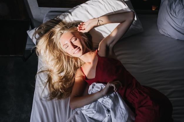 Verfijnde vrouw in rode nachtkleding die tijdens ochtendrust glimlacht. blond meisje liggend in haar bed.