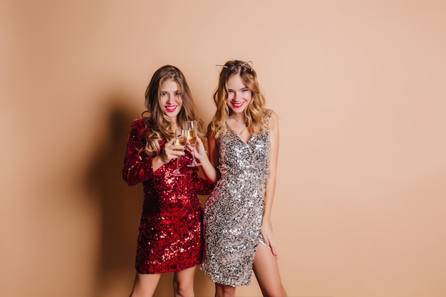 Verfijnde vrouw met zelfverzekerde glimlach poseren op kerstfeest met haar schattige zus