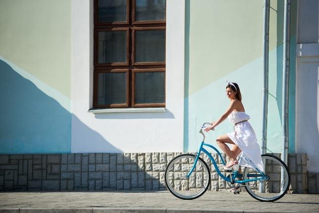Verfijnde vrouw rijdt op een hete vintage dag op een warme zomerdag in de straten van de stad op een blauwe vintage fiets