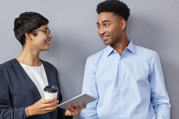 Verfijnde vrouwelijke en mannelijke collega's van gemengd ras hebben samen een gesprek