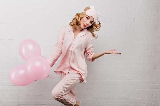 Verfijnde welgevormde vrouw in roze pyjama die met plezier danst op een witte muur. elegante feestvarken springen met helium ballonnen en lachen.