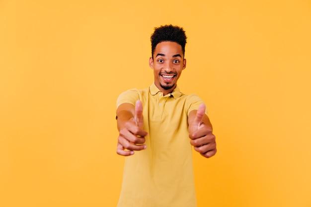 Verfijnde zwarte jongen duimen opdagen met een verbaasde glimlach. binnenfoto van goedgehumeurde afrikaanse man met grappig kapsel.