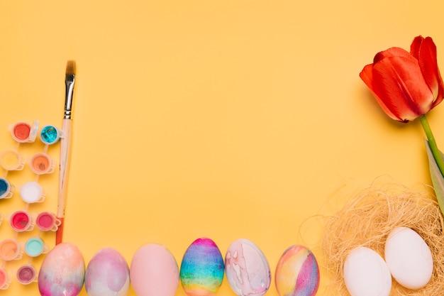 Verfkleur; penseel; rode tulp; nest en paaseieren op gele achtergrond