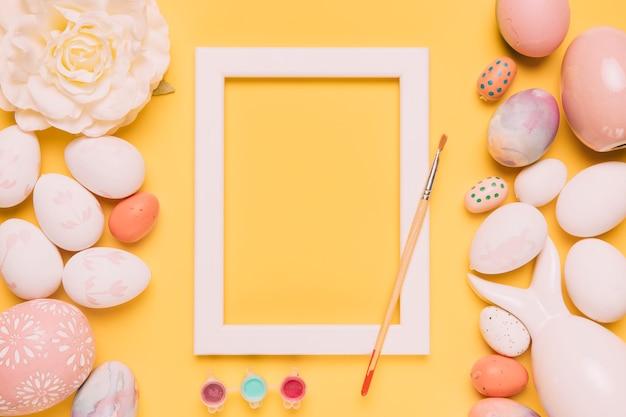 Verfkleur; penseel; wit grenskader; roos en paaseieren op gele achtergrond