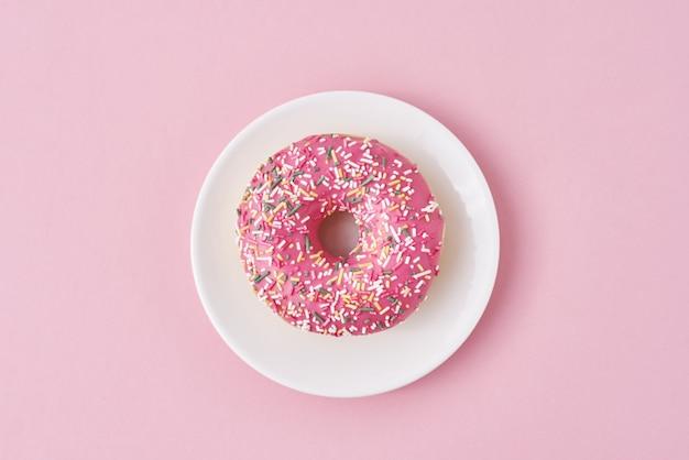 Verfraaide donat bestrooit en suikerglazuur in witte plaat op roze achtergrond. creatief en minimalis voedselconcept, plat bovenaanzicht