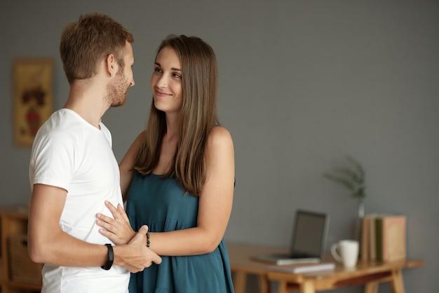 Verfraaide jonge man en vrouw die glimlachen als ze elkaar liefdevol en teder aankijken