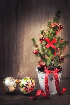 Verfraaide kerstboom en rode snuisterijen op houten achtergrond