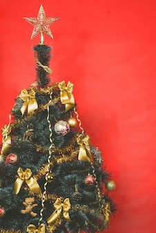 Verfraaide kerstboom met gouden lintbogen op rode achtergrond met exemplaarruimte.