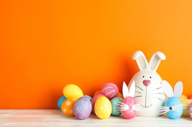Verfraaide konijntje en paaseieren op lijst tegen kleurenachtergrond