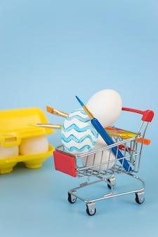 Verfraaide paaseieren en verfborstels in boodschappenwagentje met geel eierrekje dat met eieren op blauwe achtergrond wordt gevuld.