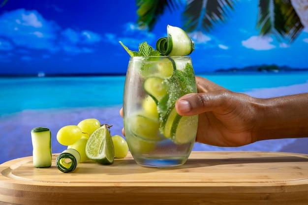 Verfrissend cocktailglas versierd met druiven, komkommer en citroen, vastgehouden door een mannenhand