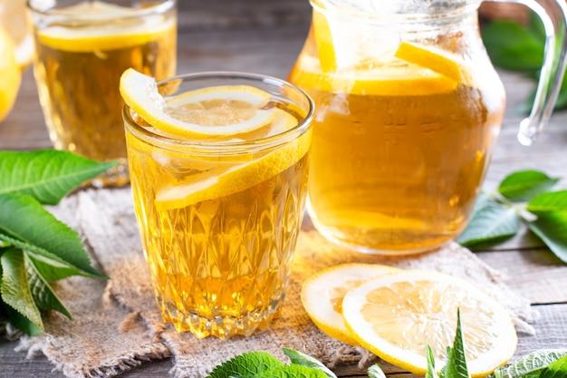 Verfrissend drankje, ijsthee met partjes limoen in glas op een houten tafel. zomerse drankjes. frisdrank