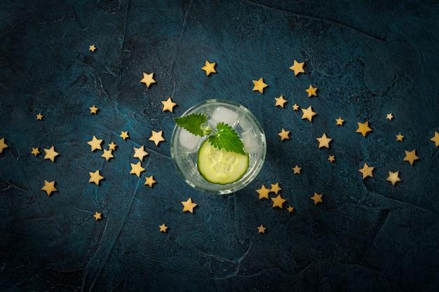 Verfrissend drankje met ijs, komkommer en munt op een donkerblauwe achtergrond met sterren. concept nachtclub, nachtleven, feest, dorst. plat lag, bovenaanzicht