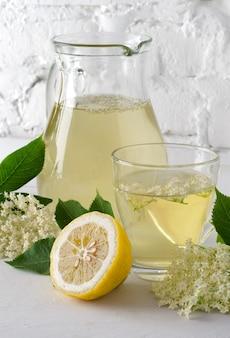 Verfrissend drankje van vlierbessenbloemen in karaf met schijfje citroen tegen witte bakstenen muur. verlies.