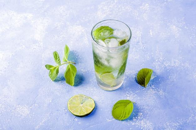 Verfrissend koel drankje met limoen en munt op blauwe tafel. zomer limonade of ijsthee in een glas. mojito cocktail met ijsblokjes.