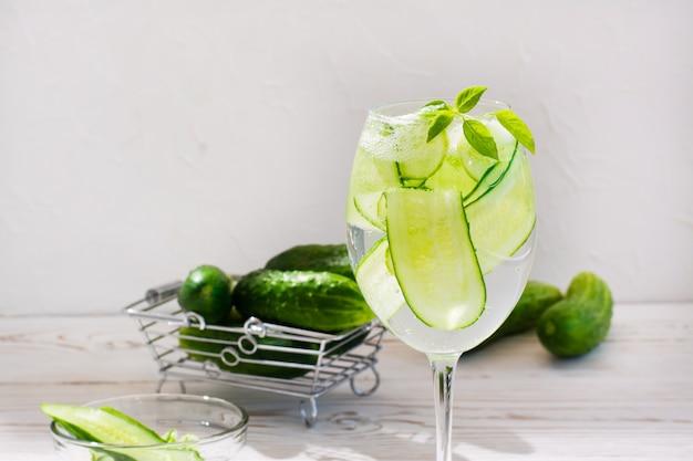 Verfrissend water met plakjes komkommer en basilicum in een glas en komkommers in een mand op een tafel