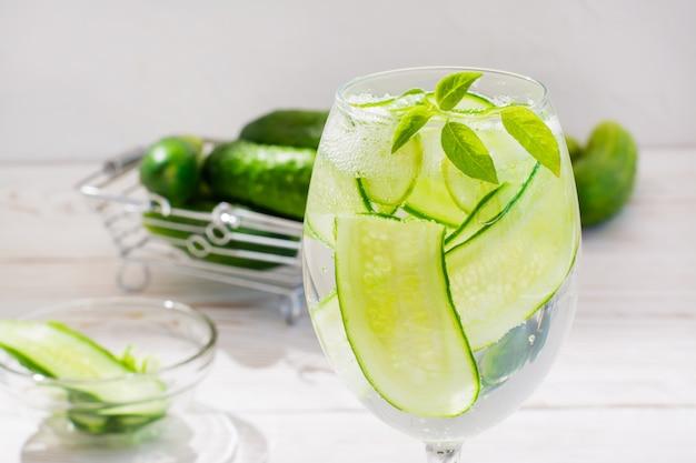 Verfrissend water met plakjes komkommer en basilicumbladeren in een glas en komkommers in een mandje