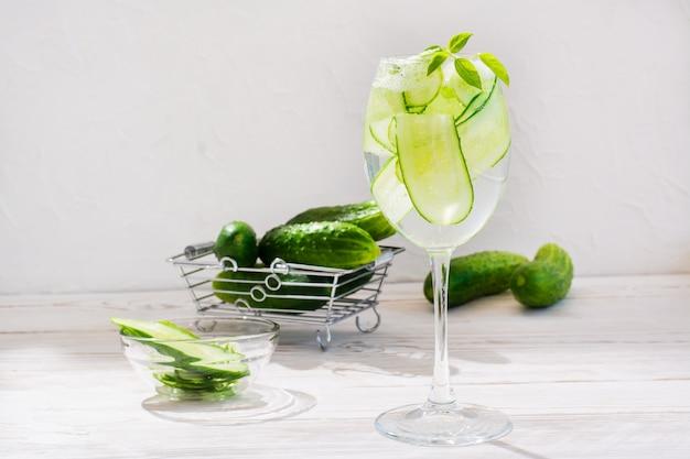 Verfrissend water met plakjes komkommer en basilicumbladeren in een glas en komkommers