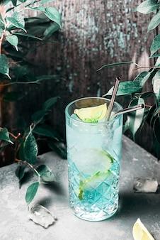 Verfrissende blauwe cocktail met limoen en ijs onder tropische bladeren.