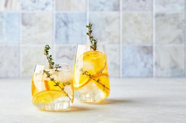 Verfrissende cocktail met ijssinaasappel en tijm verfrissende zomer zelfgemaakte alcoholische of alcoholvrije cocktail of mocktail of detox-geïnfuseerd gearomatiseerd water