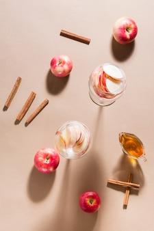 Verfrissende cocktail van appelstukjes en mineraalwater in glazen, honing en kaneel op een bruine achtergrond in fel licht. detox wellnessdrank. bovenaanzicht