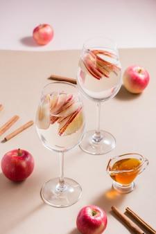 Verfrissende cocktail van appelstukjes en mineraalwater in glazen, honing en kaneel op een bruine achtergrond in fel licht. detox welzijnsdrank. verticale weergave