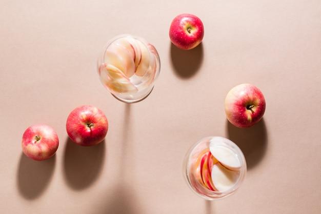 Verfrissende cocktail van appelstukjes en mineraalwater in glazen op een bruine achtergrond in fel licht. detox welzijnsdrank. bovenaanzicht
