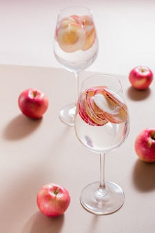 Verfrissende cocktail van appelstukjes en mineraalwater in glazen op een bruine achtergrond in fel licht. detox welzijnsdrank. verticale weergave