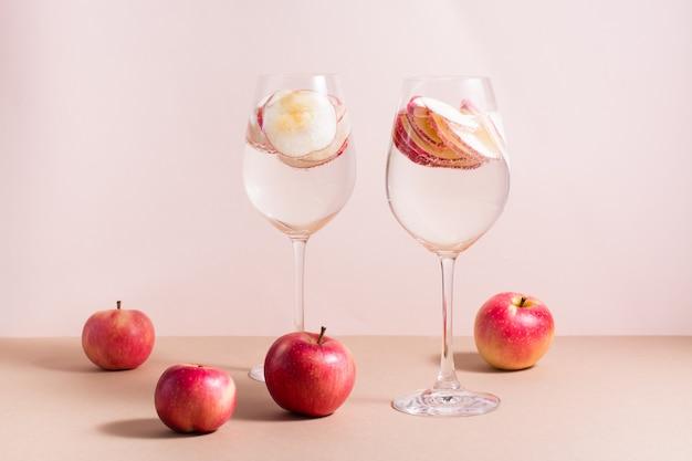 Verfrissende cocktail van appelstukjes en mineraalwater in wijnglazen op een roze achtergrond. detox wellness drankje