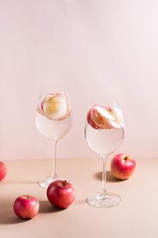 Verfrissende cocktail van appelstukjes en mineraalwater in wijnglazen op een roze achtergrond. detox wellnessdrank. verticale weergave
