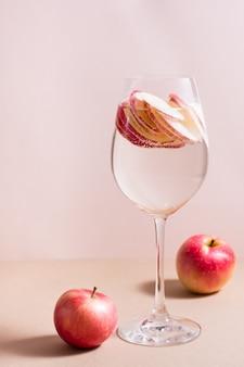 Verfrissende cocktail van stukjes appel en mineraalwater in een glas op een roze achtergrond. detox welzijnsdrank. verticale weergave