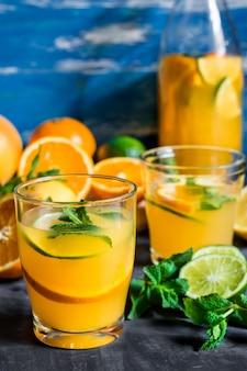 Verfrissende drank, citrus limonade sinaasappelen limoen verse munt in fles en glazen, gesneden fruit