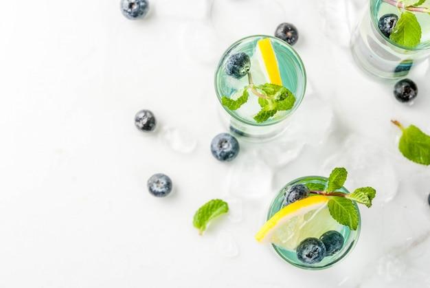 Verfrissende drankjes voor de zomer, bosbessenlimonade of mojito-cocktail met citroen, verse bosbessen en munt, wit marmer copyspace bovenaanzicht