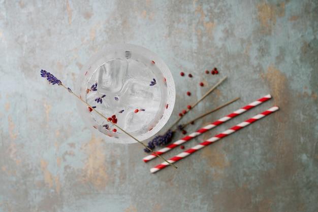 Verfrissende gin-tonic cocktail geserveerd met stro, kruiden, specerijen en ijs